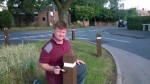 Dale Keeling re-paints the bollards/bins and subway metal fence opposite the Village Hall